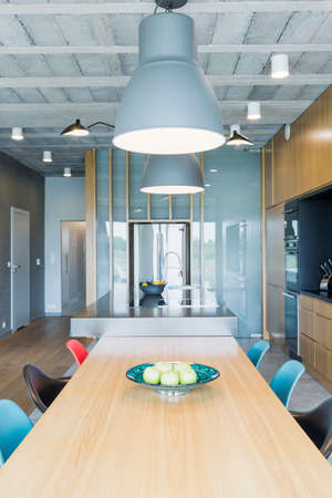 industrial design: Industrial design interior with a wooden dining table, colorful chairs and decorative lighting