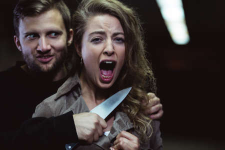 Shot of a mad man holding a knife on a screaming womans throat