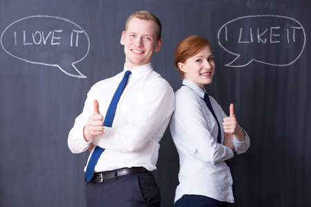 pensamiento estrategico: Happy business couple holding their thumbs up, positive quotes written on a blackboard in the background