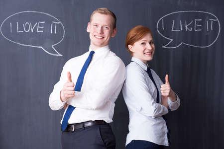 pensamiento estrategico: Par de negocios feliz celebraci�n de sus pulgares hacia arriba, citas positivas escrito en una pizarra en el fondo