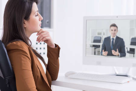 communicator: Young smartly-dressed woman in a modern, very bright office, having a video business call with a smiling young man