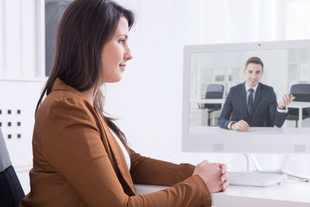 business conference: Young office worker talking with her colleague via on-line video chat