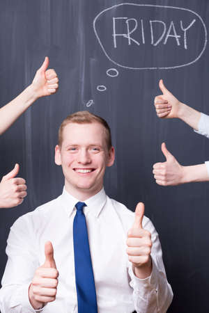 pensamiento estrategico: Happy young man holding his thumbs up, around him hands with thumbs up, friday written on a blackboard