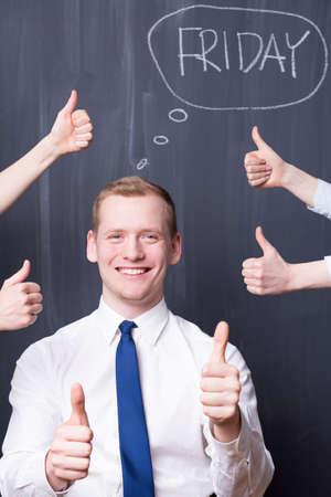 pensamiento estrategico: Hombre joven feliz que sostiene su pulgar hacia arriba, en torno a él las manos con los pulgares para arriba, viernes escrito en una pizarra Foto de archivo