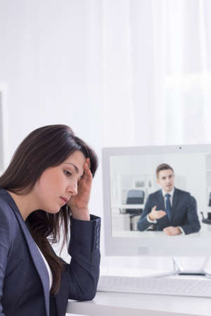 smartly: Shot of a young smartly dressed woman sitting upset in front of a computer screen where she is having a video chat