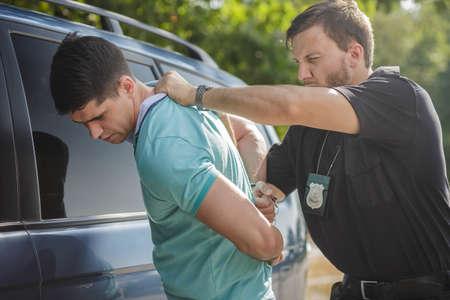 El tiro de un policía esposar a un conductor joven