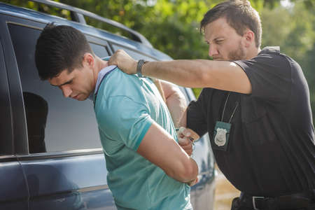 arresting: Shot of a policeman handcuffing a young driver Stock Photo