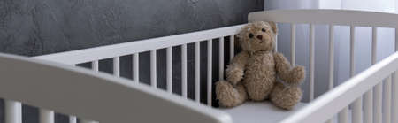baby bed: Teddy bear lying in white cot, panorama
