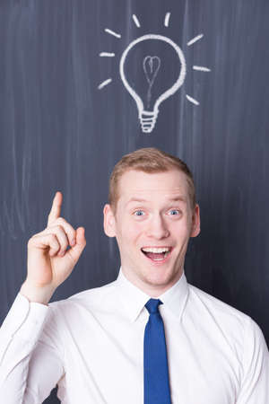 pensamiento estrategico: Happy young businessman with a light bulb over his head, blackboard in the background