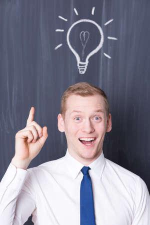 pensamiento estrategico: joven hombre de negocios feliz con una bombilla sobre su cabeza, pizarra en el fondo Foto de archivo