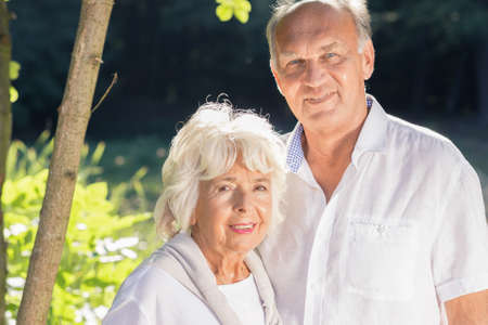 fulfilled: Beautiful portrait of an elderly couple, smiling at a camera with peaceful look on their face