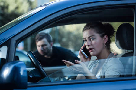 clout: Shot of a young woman sitting in a car and talking on the phone while a man sneaking towards her