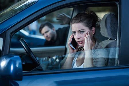 robo de autos: Captura de una mujer preocupada joven hablando por teléfono en su coche y un hombre tocando una ventana de coche detrás de su espalda