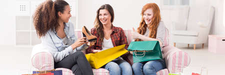 happy shopping: Happy friends sitting on a sofa with colorful shopping bags, afroamerican woman holding a shoe
