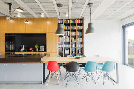 Interior in an industrial style with an open kitchen, dining table and colorful chairs Archivio Fotografico