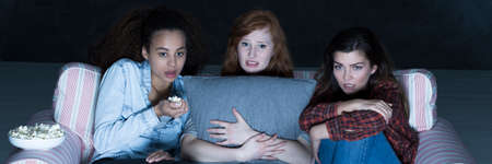 horror movies: Scared friends watching horror movies at night, sitting on a sofa, eating popcorn, ginger woman holding a pillow
