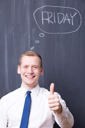 pensamiento estrategico: joven compa�ero de trabajo feliz, sosteniendo su pulgar, viernes escrito en una pizarra