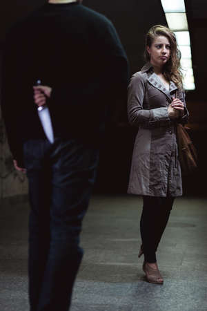 Shot of a man keeping a knife behind his back and walking towards a young woman