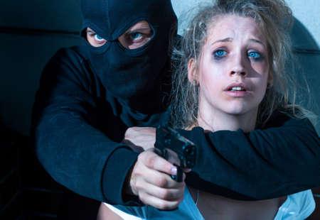 Primer plano de un bandido pasamontañas vestidos de la celebración de una mujer aterrorizada joven y apuntando con su arma a alguien