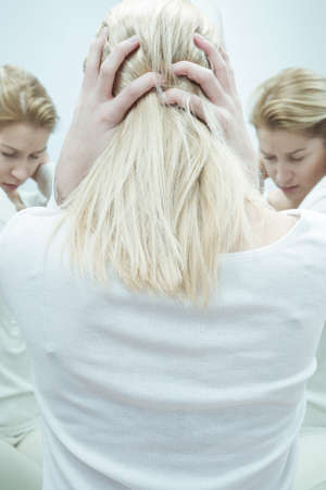 Reflection of young, blonde woman with schizophrenia.