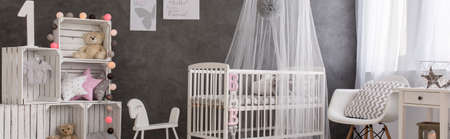 cot: Baby room with white cot, handmade shelving unit and stylish decorations Stock Photo
