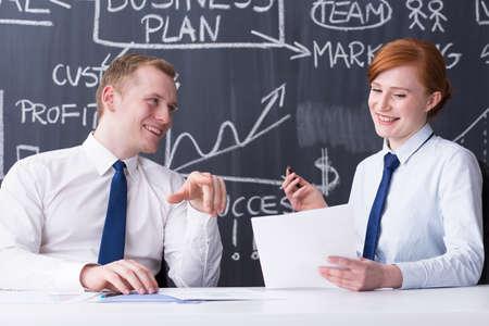 pensamiento estrategico: Feliz el hombre y la mujer que trabaja, la sonrisa y la preparación del plan de negocio, pizarra en el fondo Foto de archivo