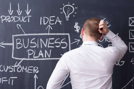 pensamiento estrategico: El hombre vista posterior rascándose la cabeza, plan de negocios dibujado en una pizarra en el fondo