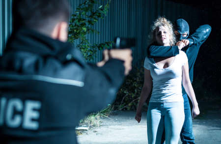 pointing gun: Thief holding a woman hostage while a policeman is pointing gun at him