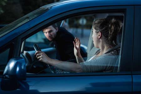 robo de autos: Captura de una mujer asustada que grita mientras que un extraño se está metiendo en su coche