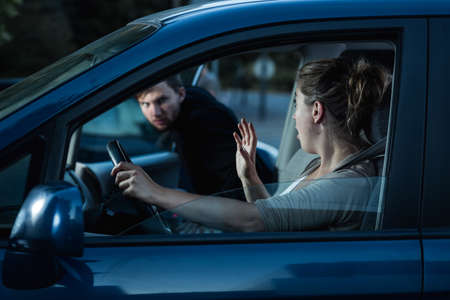 clout: Shot of a  scared woman screaming while a stranger is getting into her car Stock Photo