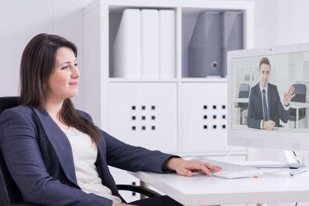 Joven, elegantemente vestido empleado de oficina sonriendo a su interlocutor en línea visible en la pantalla del ordenador