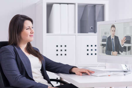 Young, smartly dressed office worker smiling at her on-line interlocutor visible on the computer screen