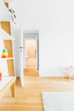wood flooring: Spacious and light child room with hardwood flooring and simple furniture