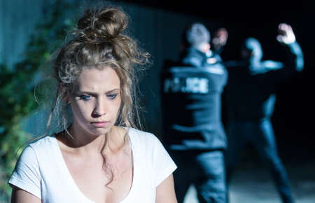 Close-up of a devastated hijack survivor and her assaulter surrendering to a policeman in the blurry background