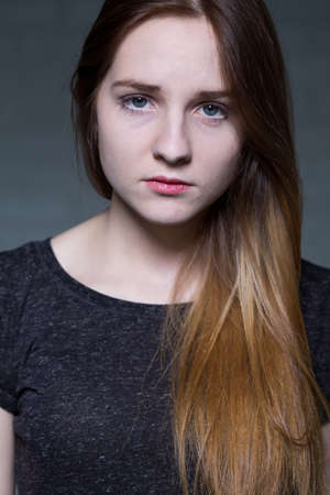 young woman face: Portrait of young pretty  angry teenage girl in adolescence age. Looking to the camera and standing on a grey background