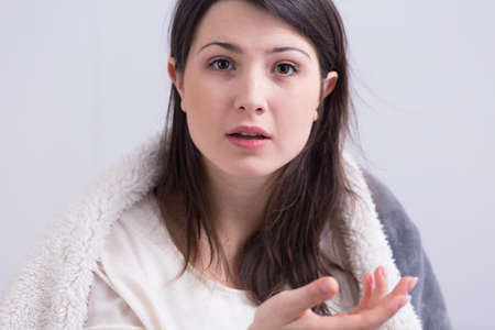 young woman face: Portrait of a young woman covered with furry blanket, looking at the camera with a confused look on her face Stock Photo