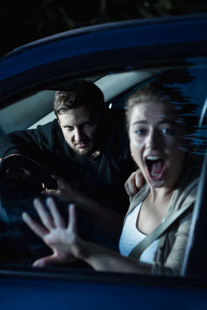 clout: Shot of a young woman screaming and a man sitting behind her in a car