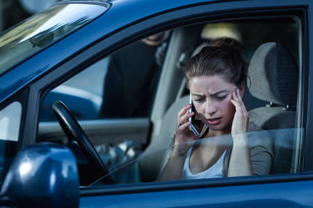 carelessness: Shot of a young woman talking on the phone and a man standing behind her car Stock Photo