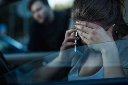 carelessness: Shot of a young woman talking on the phone and covering her face and a man standing next to the car
