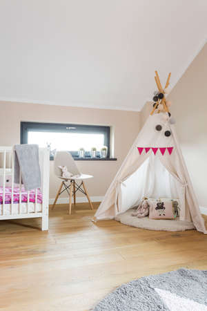 flooring: Cozy child room with a wood flooring, small window and wigwam play tent