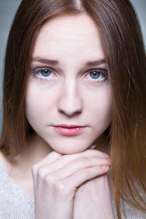 express feelings: Close-up of pretty young serious girl looking to the camera. Leaning her chin on hands