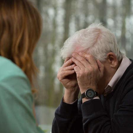 hombre anciano llorando durante la visita de un psiquiatra Foto de archivo