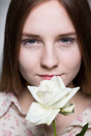 express feelings: Young innocent pretty girl holding white beautiful flower. Posing on a grey background