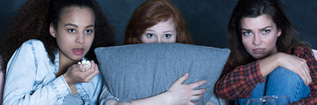 horror movies: Three friends watching horror movies, eating popcorn, ginger woman covering face with a pillow, panorama