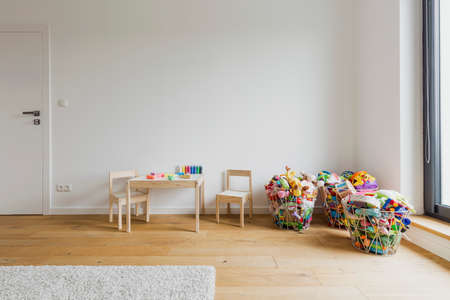 wood flooring: Light child room with a small table, two chairs and  toy baskets