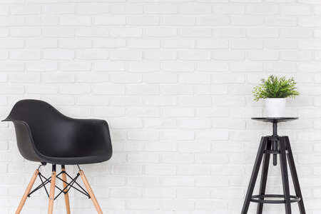 comfort room: Black chair and plant in a pot standing on a small table, brick wall in the background Stock Photo