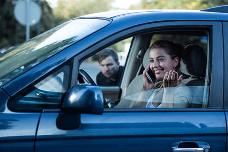 clout: Shot of a happy young woman sitting in her car and a man sneaking towards her