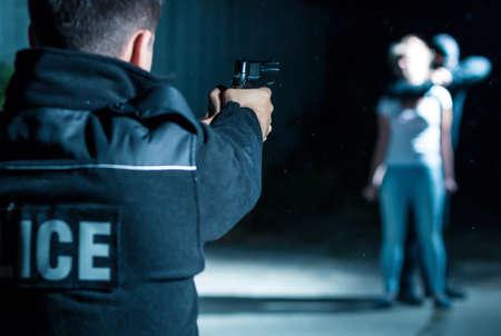 Primer plano de un policía apuntando con su arma a un ladrón que sostiene un rehén