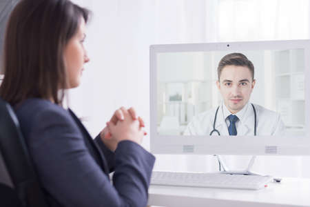 smartly: Shot of a smartly dressed woman having an on-line video conversation with a medical doctor