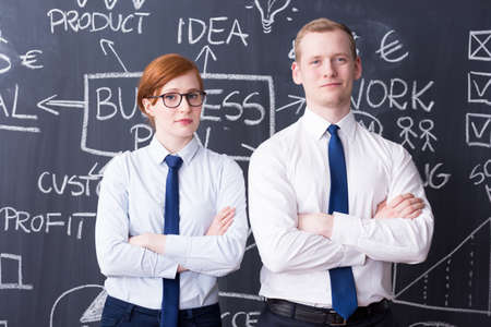pensamiento estrategico: ambicioso joven y mujer de pie junto a la otra, plan de negocios realizado en una pizarra en el fondo